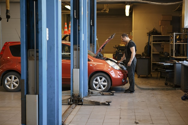 Professional mechanic repairing car engine in garage.