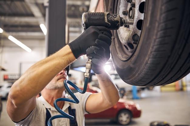 차고에서 자동차 바퀴 디스크를 수리하는 전문 정비사