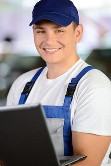 Professional mechanic using a laptop computer.