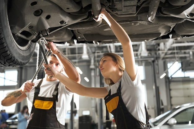 Professional mechanics standing under automobile and working