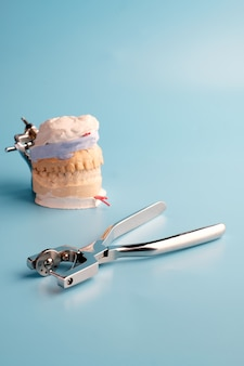 Professional medical dentists instruments on blue table.