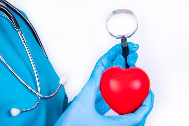虫眼鏡を持っている専門医が赤いハートボールをチェックします。ヘルスケアの概念。