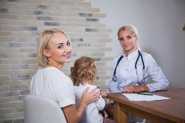 白い制服を着た専門の小児科医が母親に娘と相談します。子供の患者の良好な関係の信頼の概念を持つ小児科医