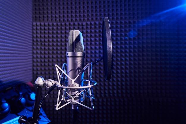 Профессиональный микрофон крупным планом на фоне студии звукозаписи