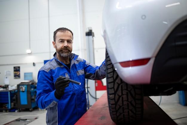 ブレーキとディスクをチェックするプロの中年のひげを生やした白人の自動車整備士。