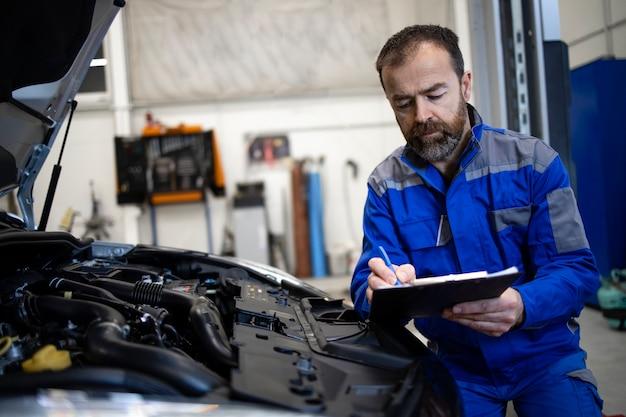フードが開いた状態で車両のエンジンエリアのそばにチェックリストが立っているプロの中年の白人自動車整備士が故障を検出します。