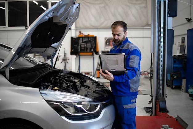 ラップトップコンピューター診断ツールを備えたプロの中年の白人自動車整備士が、フードが開いた状態で車両のエンジン領域のそばに立って、誤動作を検出します。
