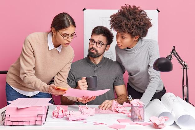 Профессиональные эксперты смешанной расы обсуждают будущий проект и чертежи во время совместной работы в офисе, консультируются друг с другом по важным вопросам, возникающим на рабочем столе с бумагами. концепция работы в команде