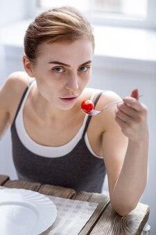 Профессиональная модель. грустная молодая женщина наблюдает за своим весом, будучи профессиональной моделью