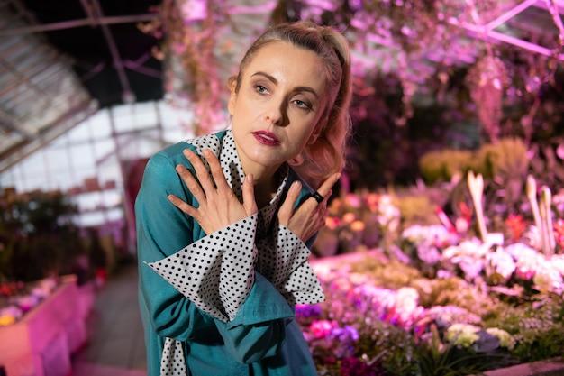 プロフェッショナルモデル。写真を撮られながらクロスハンドで立っている真面目な魅力的な女性