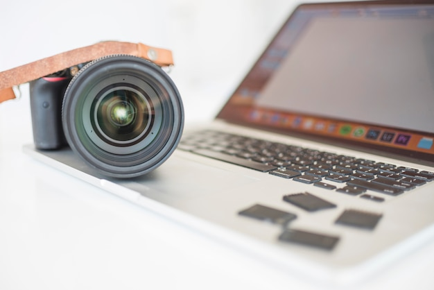 Professional modern camera and memory cards on laptop