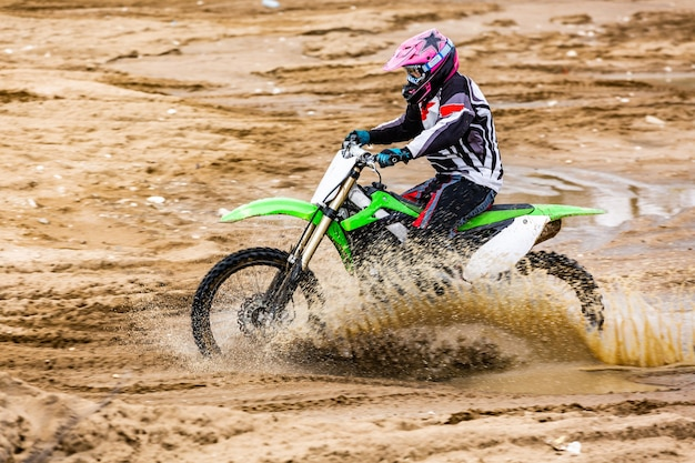 Professional motocross motorcycle rider drives over the dirt road track.