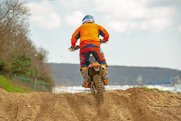 Professional motocross motorcycle rider drives over the road track.