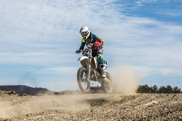 Professional motocross motorcycle rider drives through smoke and mist over the dirt road track.