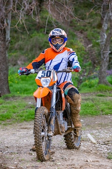 Professional motocross rider drives over the dirt road track