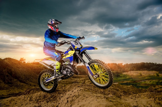 Professional motorcycle rider driving on the mountains and further down the off-road track