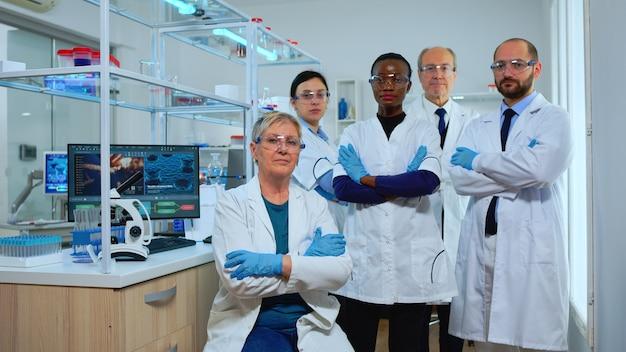 近代的な設備の整ったラボでカメラを見ているプロの多民族医療スタッフ。ハイテク、科学研究のための化学ツール、ワクチン開発でウイルスの進化を調べる医師のチーム