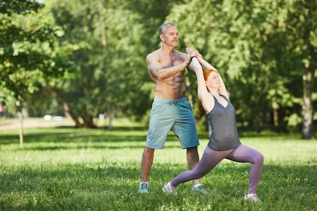 サマーパークで練習しながら女性のヨガポーズを調整するプロの筋肉に縛られたトレーナー