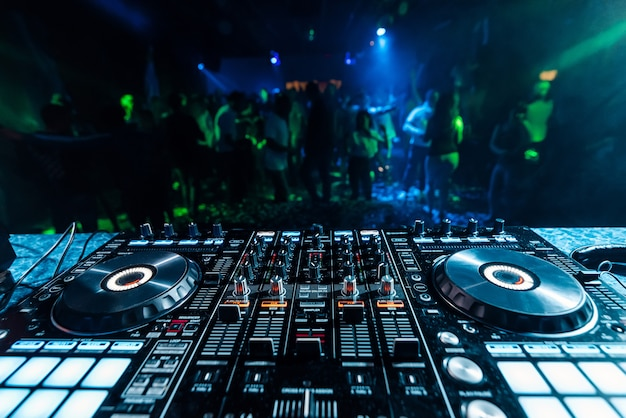 Professional music dj mixer in a booth in a nightclub on the background of blurred silhouettes of dancing people