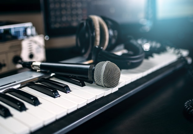 Professional music studio equipment, closeup. musical keyboard, microphone and headphones.