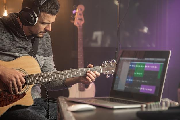 스튜디오에서 전문 음악가 녹음. 녹음 스튜디오에서 노트북 모니터 앞에 헤드폰으로 앉아 기타리스트를 닫습니다.