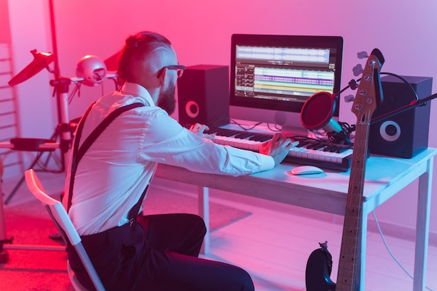 Professional musician recording synthesizer in digital studio at home, music production technology