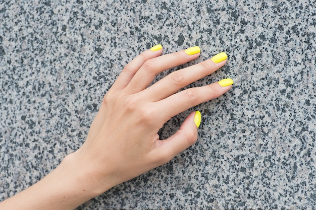 Professional nail care. female hand with yellow nail color. applying nail lacquer. nail salon manicure. acrylic overlays and extensions. cosmetic beauty treatment for fingernails.