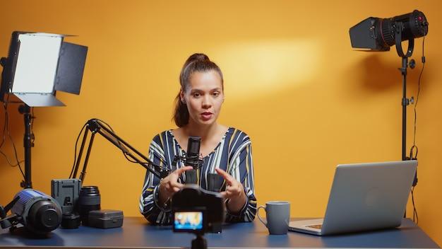 그녀의 스튜디오 세트에서 뉴 미디어 스타의 전문 np-f 배터리 리뷰. 온라인 인터넷 웹 쇼를 위한 전문 비디오 사진 장비를 말하는 소셜 미디어의 콘텐츠 제작자 뉴 미디어 스타 인플루언서