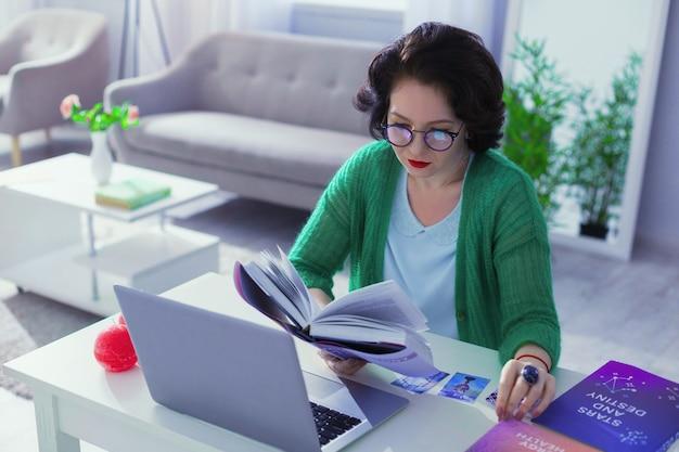 Профессиональный нумеролог. симпатичная красивая женщина изучает специальную литературу, работая нумерологом