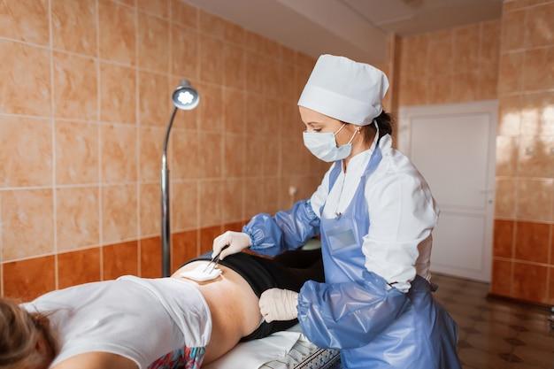 Профессиональная медсестра меняет повязку на пациента, который лежит на кушетке в отделении неотложной помощи. спина в синяках. травма спины.