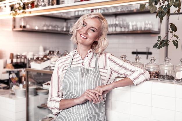 専門職。パン屋で働いている間カウンターに立っている幸せなポジティブな女性