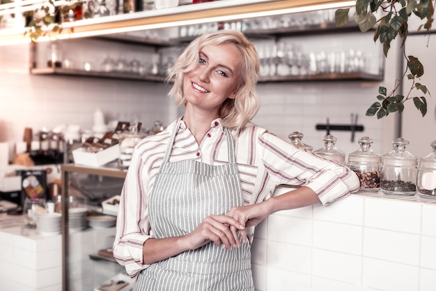 Professional occupation. happy positive woman standing at the counter while working in a bakery