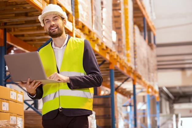 전문 직업. 큰 창고에서 일하는 동안 웃고있는 스마트 물류 관리자