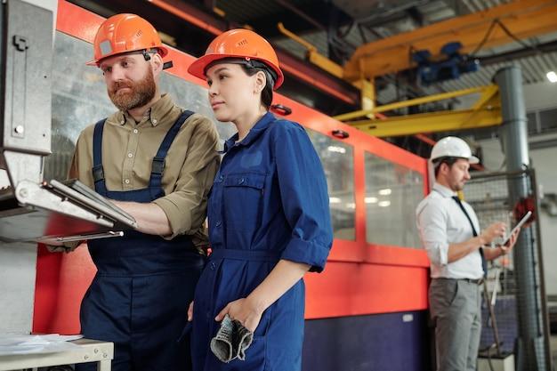 ワークショップでアジアの労働者にcncマシンの機能を説明する産業プラントの専門家