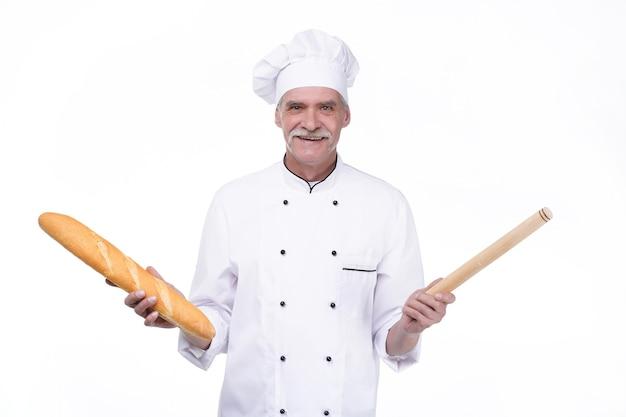 白い壁に滞在しながらバゲットを保持している制服を着たプロの古いパン屋
