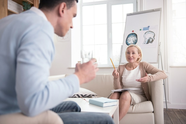 Professional opinion. successful mature psychologist using notebook while helping man