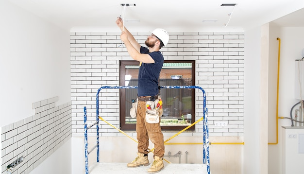 Professional in overalls with tools on the repair site full length. home renovation concept.