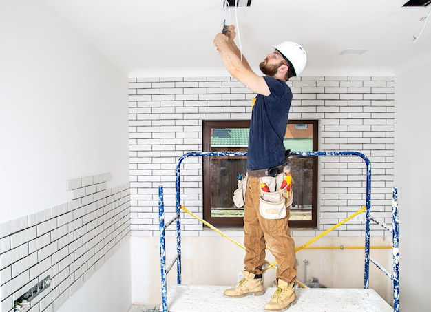 Professional in overalls with tools on the repair site. home renovation concept.