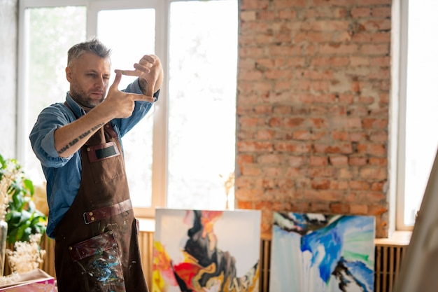 Professional painter in apron looking at painting on easel through frame made up of fingers in studio