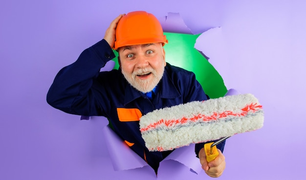 紙の穴を通して見ているペイントローラーを持つプロの画家またはデコレータ。修理と建物のコンセプト。