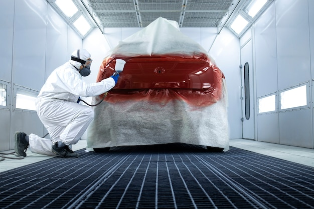 Professional painter in protective clothing applying varnish layer and finishing painting of the car