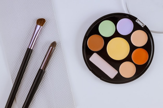 Professional pallet of eyeshadow multicolor bright make up on isolated white table