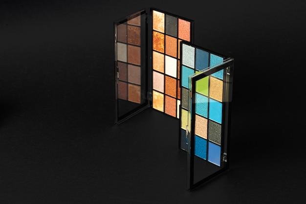 Профессиональная палитра теней для век. разноцветные рассыпанные тени для век на черном столе. закройте вверх.