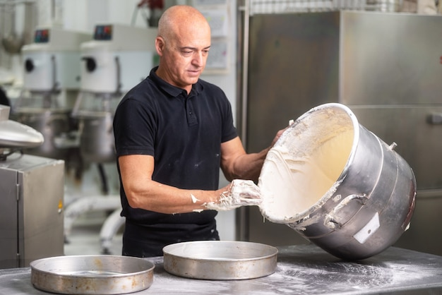 Professional pastry chef whisking cream in big casserole at pastry shop kitchen.
