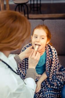 전문 소아과 의사. 전문 여성 소아과 의사가 그녀의 목을 검사하는 즐거운 빨간 머리 소녀