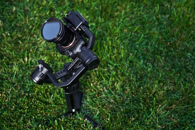 Professional photo and video camera close-up on a background of green grass