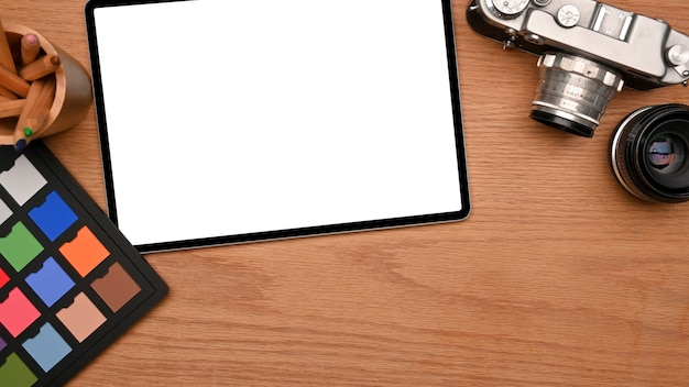 Professional photographer desk with digital tablet blank screen mockup camera and colour checker