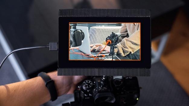 젊은 콘텐츠 제작자를 녹화하는 외부 디스플레이가있는 카메라를 들고있는 전문 사진 작가