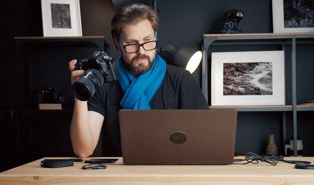 机に座ってノートパソコンの画面を見ながら片手でカメラを保持しているプロの写真家