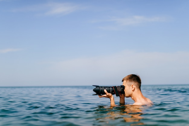 Professional photographer  job concept. boy working in difficult conditions. adult man swimming in sea with  huge phocamera and big lense above.  male in ocean holding waterproof camera on vacation.